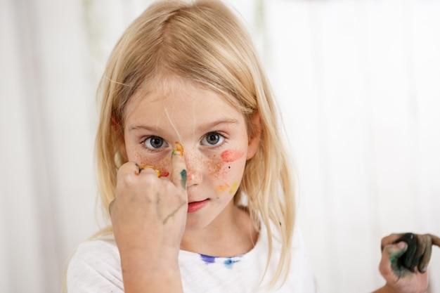 Ritratto di bambino simile ad un angelo con macchie colorate di vernice sul viso Foto Gratuite