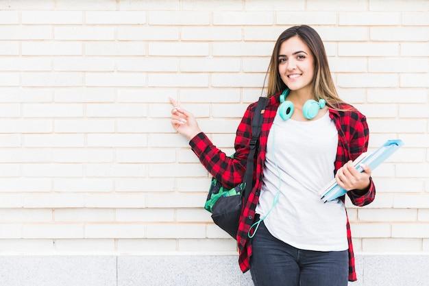 Ritratto di bei libri sorridenti della tenuta della studentessa e zaino di trasporto sulla spalla che indica il suo dito contro il muro di mattoni bianco Foto Gratuite