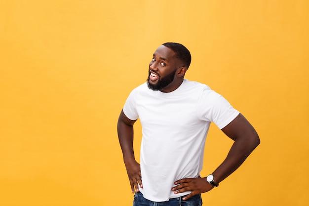 Ritratto di bel ragazzo africano giovane sorridente in t-shirt bianca su sfondo giallo Foto Premium