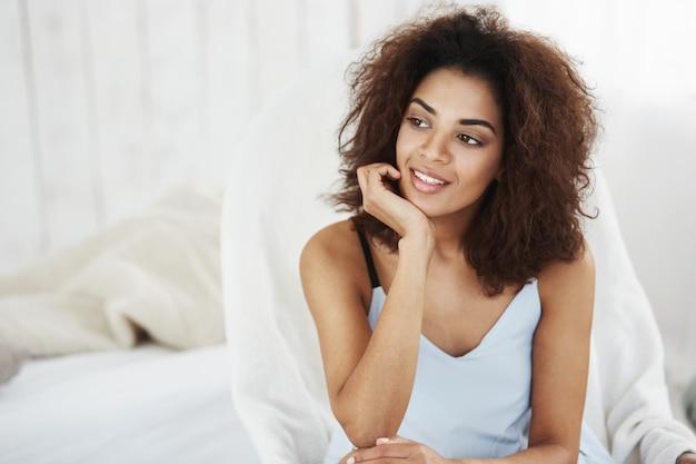 Ritratto di bella donna africana vaga nella seduta sorridente degli indumenti da notte nella sedia a casa. copia spazio. Foto Gratuite