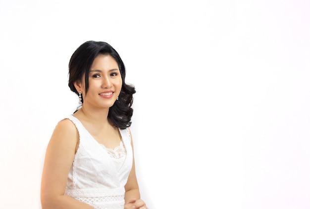 Ritratto di bella donna asiatica lunga dei capelli neri che sorride alla macchina fotografica contro il fondo bianco Foto Premium