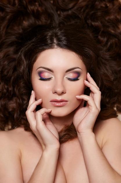 Ritratto di bella donna bruna con lunghi capelli ricci e trucco luminoso Foto Gratuite