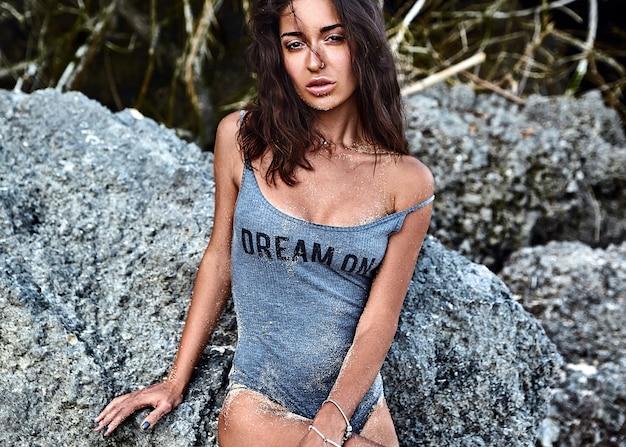 Ritratto di bella donna caucasica modello preso il sole con i capelli lunghi scuri in costume da bagno in posa vicino a rocce sulla spiaggia Foto Gratuite