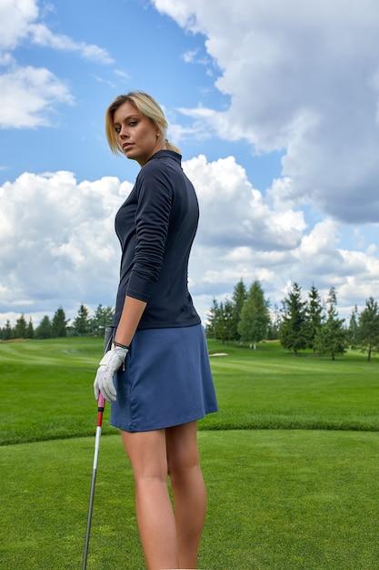 Ritratto di bella donna che gioca a golf su un fondo verde del campo all'aperto. il concetto di golf, la ricerca dell'eccellenza, l'eccellenza personale, lo sport reale. Foto Premium