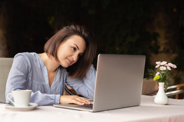 Ritratto di bella donna che lavora da casa, si siede con una tazza di caffè al tavolo, lavorando sul portatile in casa Foto Premium