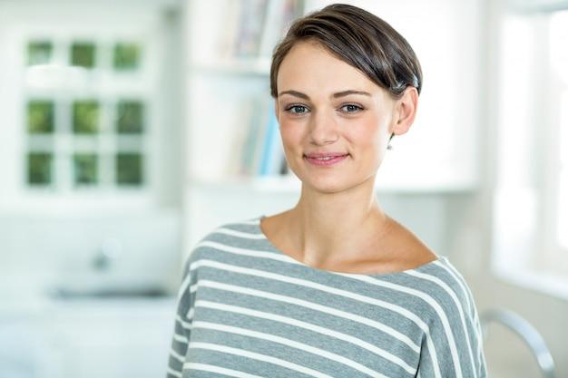 Ritratto di bella donna che sta nella cucina Foto Premium