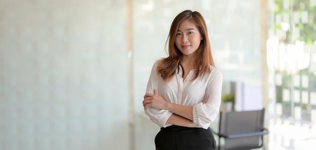 Ritratto di bella donna d'affari asiatiche in piedi nella stanza ufficio e sorridendo alla telecamera Foto Premium