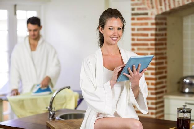 Ritratto di bella donna in accappatoio che si siede sul piano di lavoro della cucina e utilizzando la tavoletta digitale mentre uomo stiratura vestiti dietro di lei Foto Premium