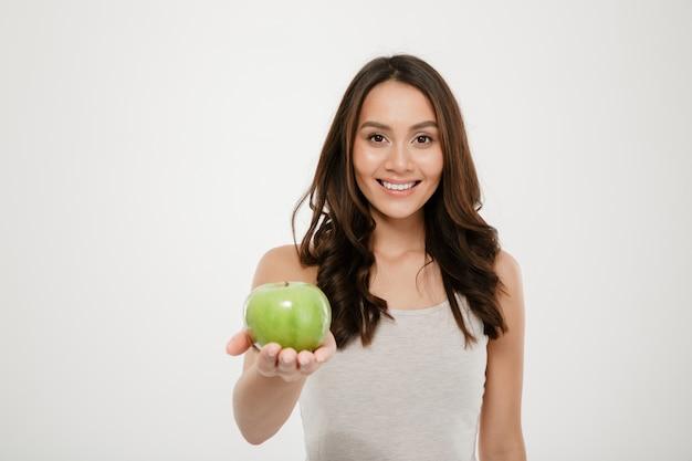Ritratto di bella donna in buona salute che sorride e che mostra mela succosa verde sulla macchina fotografica, isolata sopra bianco Foto Gratuite
