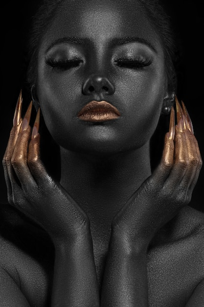 Ritratto di bella donna in oro e colori neri Foto Premium