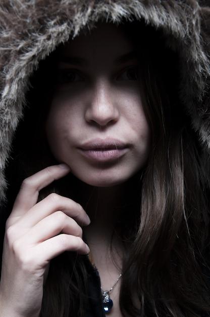 Ritratto di bella donna in piedi e guardando in giacca nera con cappuccio peloso Foto Gratuite