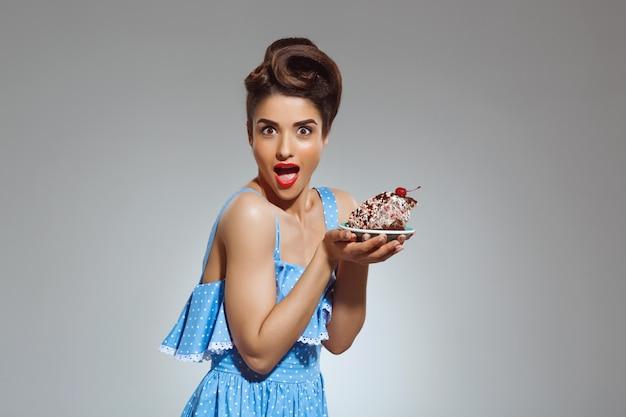 Ritratto di bella donna pin-up tenendo la torta nelle mani Foto Gratuite