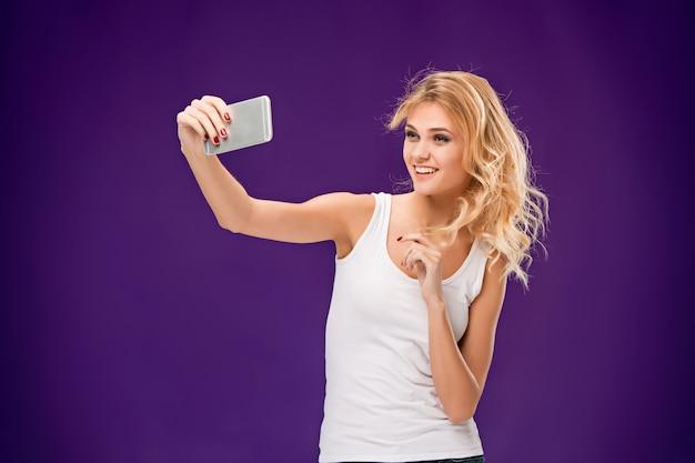 Ritratto di bella donna sorridente che prende selfie Foto Gratuite