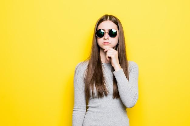 Ritratto di bella donna sorridente in occhiali da sole e vestito contro della parete gialla Foto Gratuite