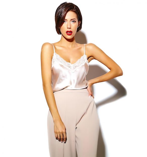 Ritratto di bella felice carina donna bruna sexy con le labbra rosse in pantaloni larghi classici su sfondo bianco Foto Gratuite
