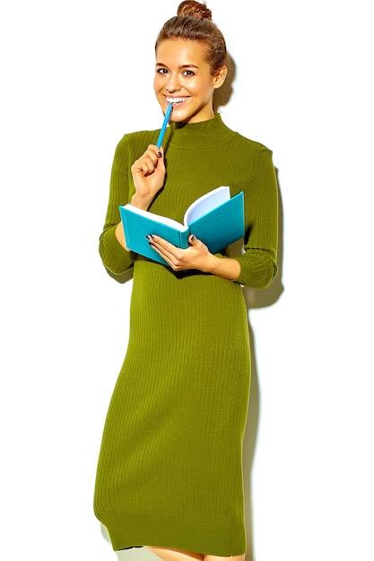 Ritratto di bella felice carina ragazza sorridente donna bruna in abiti casual casual verde hipster estate isolata on white pungente penna blu con notebook colorato Foto Gratuite