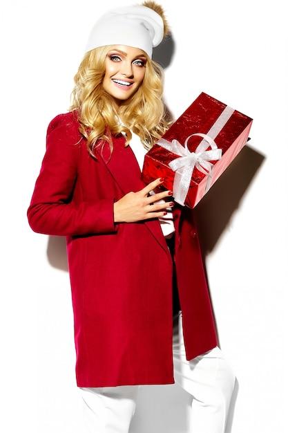 Ritratto di bella felice dolce ragazza bionda donna sorridente che tiene nelle sue mani grande confezione regalo di natale in abiti invernali casual rosso hipster Foto Gratuite