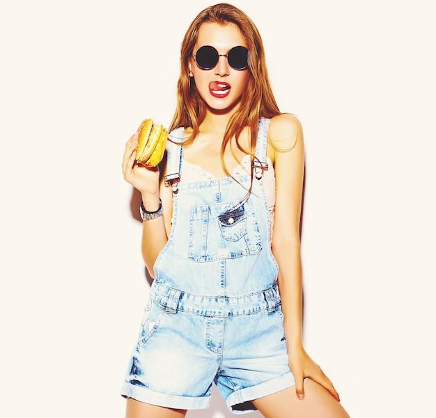 Ritratto di bella giovane donna alla moda che mangia hamburger Foto Gratuite