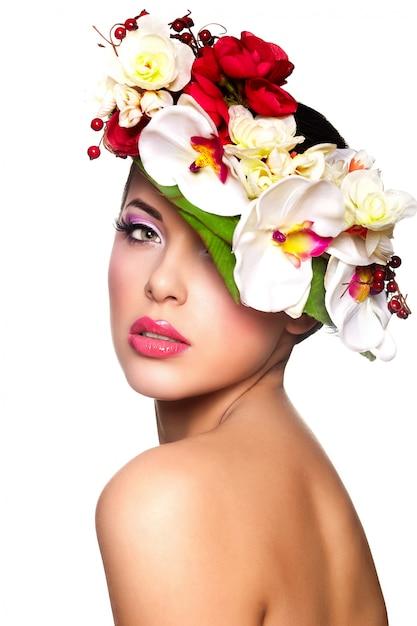 Ritratto di bella giovane donna alla moda con i fiori variopinti sulla testa Foto Gratuite