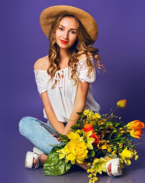 Ritratto di bella giovane donna bionda in elegante cappello estivo di paglia che tiene bouquet di fiori primaverili colorati vicino a sfondo muro viola. Foto Gratuite