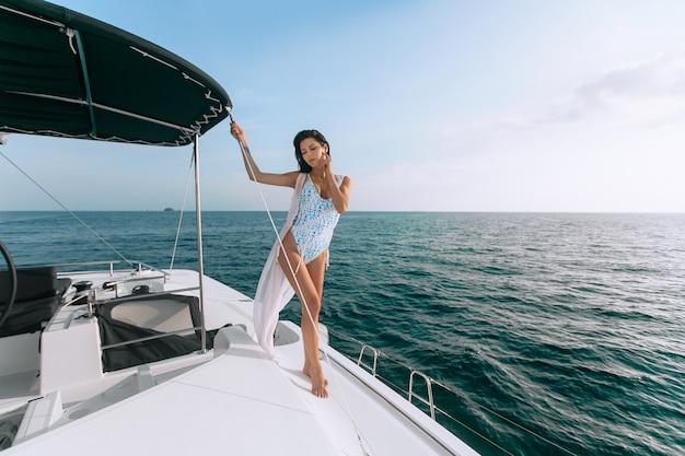 Ritratto di bella giovane donna di modo che sta e che posa sulla barca a vela o sull'yacht Foto Premium