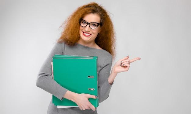 Ritratto di bella giovane donna di redhead in vestiti grigi in vetri che tengono le cartelle sulla parete grigia Foto Premium