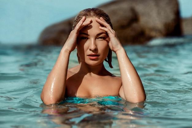 Ritratto di bella giovane donna sensuale nella fine dell'acqua di mare su. il modello fissa nella fotocamera. moda Foto Premium