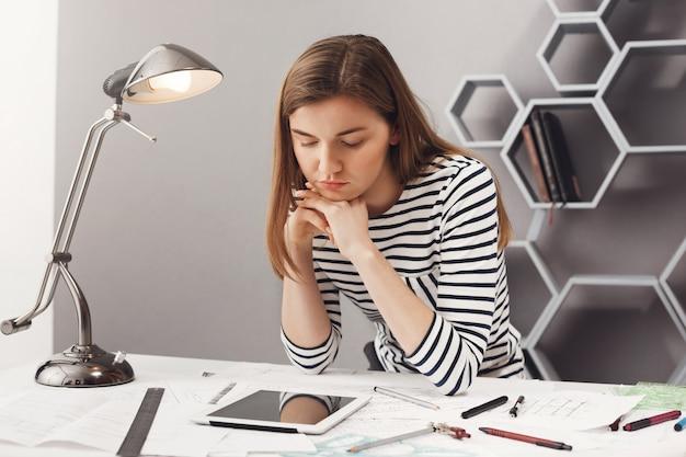 Ritratto di bella giovane studentessa architetto seria con i capelli castani in look a strisce da vicino, tenendo la testa con le mani, guardando in tavoletta digitale con espressione del viso stanco, cercando un esempio Foto Gratuite