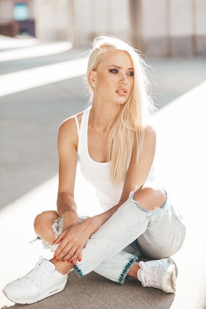 Ritratto di bella ragazza bionda carina in maglietta bianca e jeans in posa all'aperto. ragazza sveglia che si siede sull'asfalto sulla strada Foto Gratuite