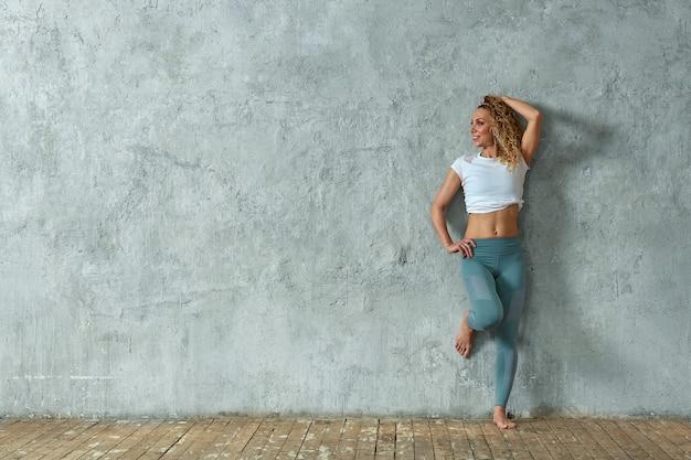 Ritratto di bella ragazza bionda sexy che sorride, su sfondo grigio Foto Premium