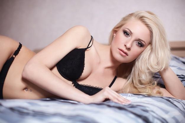 Ritratto di bella ragazza bionda sexy sdraiato sul letto in lingerie nera con trucco luminoso e acconciatura Foto Gratuite