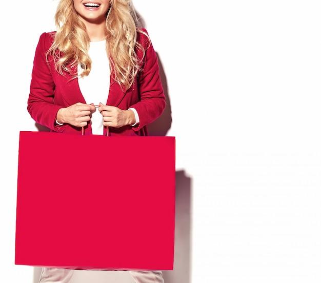 Ritratto di bella ragazza felice felice dolce sorpresa bionda donna con in mano grande borsa della spesa in abiti rossi hipster isolato su bianco Foto Gratuite