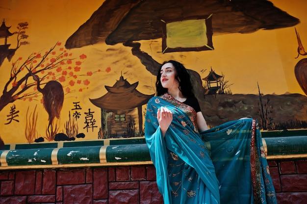 Ritratto di bella ragazza indiana di brumette o modello indù della donna contro la parete giapponese dei grafiti. Foto Premium