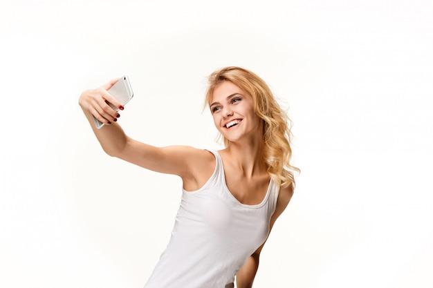 Ritratto di bella ragazza sorridente con il telefono moderno Foto Gratuite