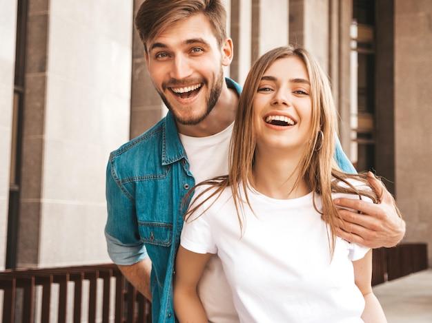 Ritratto di bella ragazza sorridente e il suo bel ragazzo. donna in abiti casual jeans estivi. . abbracciare Foto Gratuite