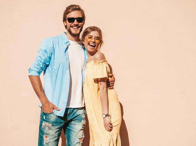Ritratto di bella ragazza sorridente e il suo bel ragazzo. donna in abito estivo casual e uomo in jeans. famiglia felice e allegra. femmina divertirsi in strada vicino al muro Foto Gratuite