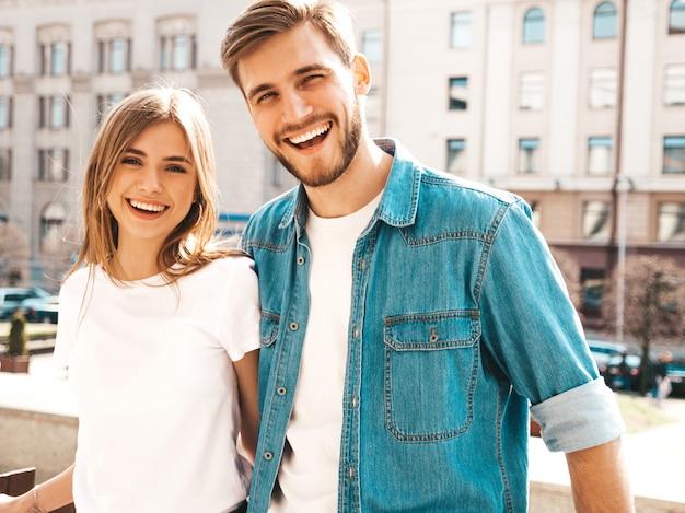 Ritratto di bella ragazza sorridente e il suo bel ragazzo in abiti estivi casual. . abbracciare Foto Gratuite