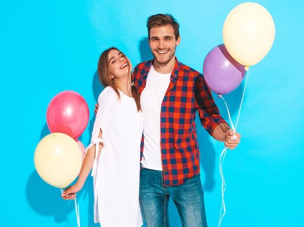 Ritratto di bella ragazza sorridente e il suo bel ragazzo tenendo un mazzo di palloncini colorati e ridendo. coppia felice. buon compleanno Foto Gratuite