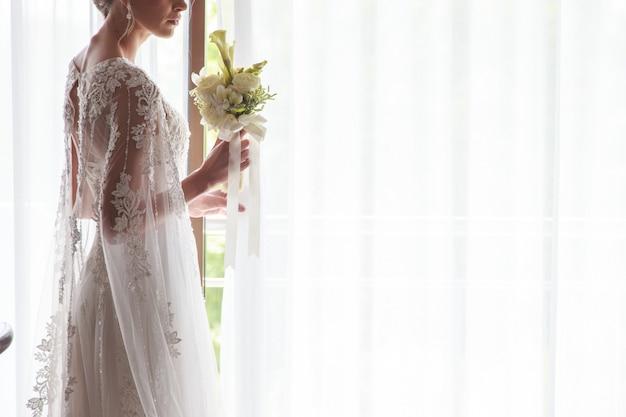 Ritratto di bella sposa che tiene il mazzo vicino alla finestra al chiuso Foto Premium