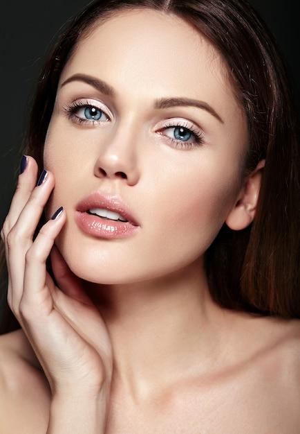 Ritratto di bellezza del primo piano di fascino di bello modello caucasico sensuale della giovane donna con trucco nudo che tocca la sua pelle pulita perfetta che posa sul fondo scuro Foto Gratuite