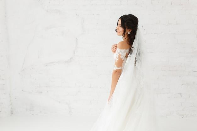 Ritratto di bellezza della sposa che indossa il vestito da sposa moda con piume Foto Gratuite