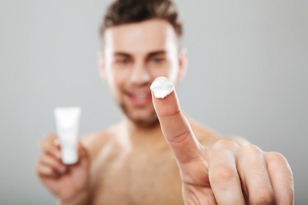 Ritratto di bellezza di un uomo mezzo nudo applicando la crema per il viso Foto Gratuite