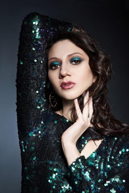 Ritratto di bellezza di una donna con un bel trucco da sera, donna bruna in un abito da sera lucido con paillettes. cosmetici naturali per il viso Foto Premium