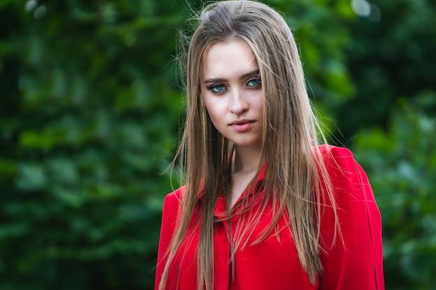 Ritratto di bellezza di una giovane e bella ragazza con lunghi capelli lisci che volano. capelli magnifici. ritratto a colori vestito rosso. Foto Premium