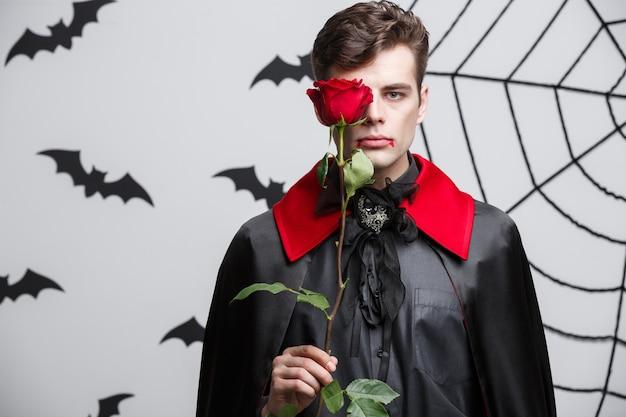 Ritratto di bello caucasico vampiro che tiene bella rosa rossa. Foto Premium