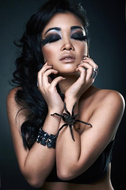 Ritratto di bello giovane modello asiatico sexy con il ragno Foto Premium