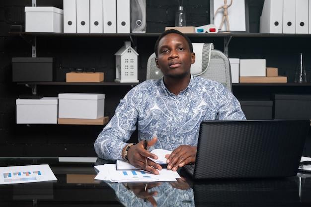 Ritratto di bello giovane uomo d'affari afroamericano che lavora con i documenti e computer portatile in ufficio Foto Premium