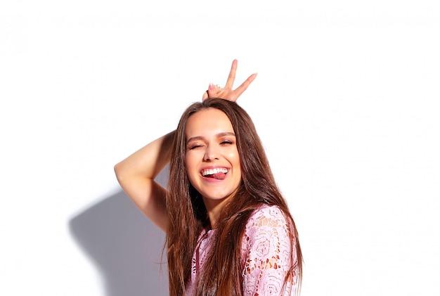 Ritratto di bello modello caucasico sorridente della donna del brunette in vestito alla moda da estate dentellare luminosa isolato su priorità bassa bianca. mostrando la sua lingua e il segno di pace Foto Gratuite
