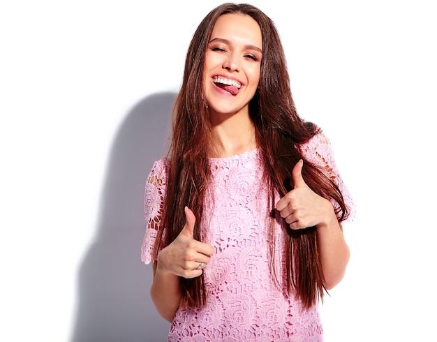 Ritratto di bello modello caucasico sorridente della donna del brunette in vestito alla moda da estate dentellare luminosa isolato su priorità bassa bianca. mostrando la sua lingua, pollice in alto Foto Gratuite