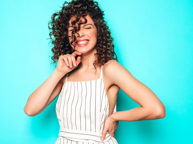 Ritratto di bello modello sorridente con l'acconciatura dei riccioli di afro vestita in vestiti dei pantaloni a vita bassa di estate ragazza spensierata sexy che posa vicino alla parete blu donna divertente e positiva alla moda Foto Gratuite